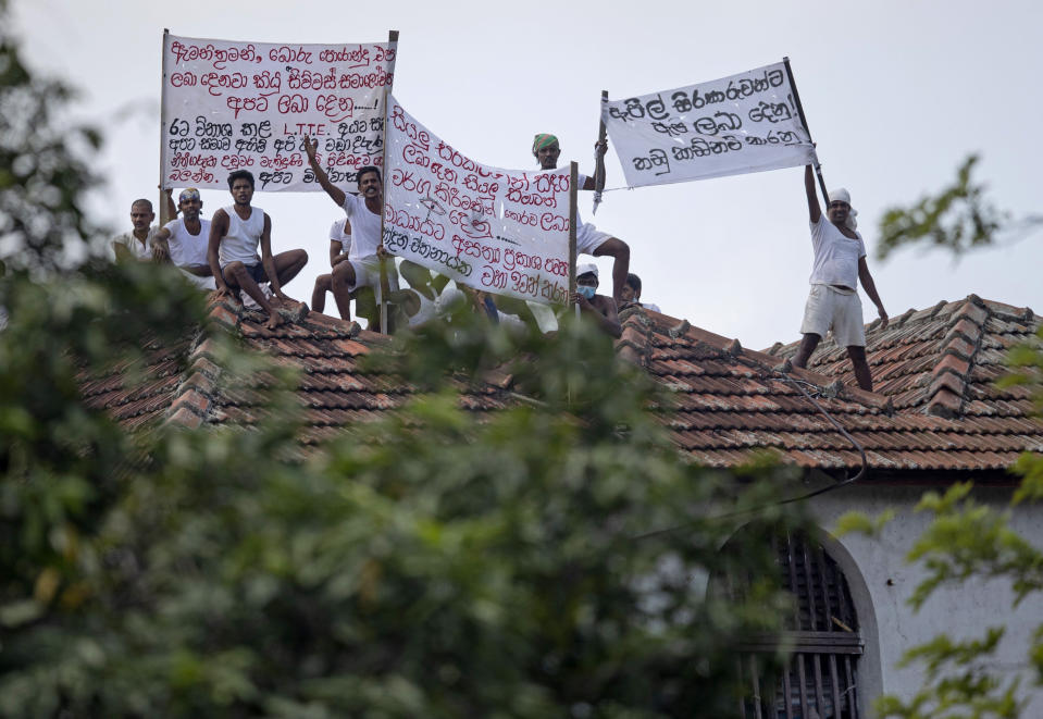 """Death-row inmates of Sri Lanka's Welikada prison protest holding banners from the roof of the prison in Colombo, Sri Lanka, Friday, June 25, 2021. About 150 death-row inmates in Sri Lanka began a hunger strike to demand their sentences be commuted, prison officials said, after the nation's president pardoned a former lawmaker who had been condemned for an election-related killing. Banners read """"Treat all inmates equally,"""" """"Grant bail on appeal applications,"""" """"Minister! Stop bogus promises,"""" """"Grant pardon to us like you did to terrorists and notorious politicians."""" (AP Photo/Eranga Jayawardena)"""