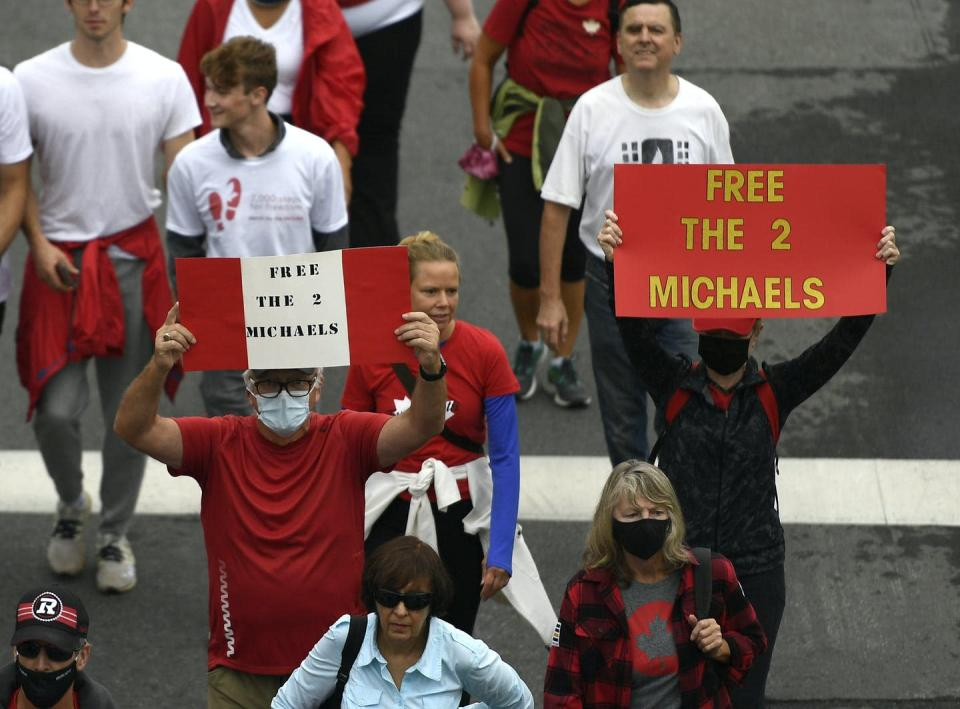 People hold signs in Ottawa calling for the release of the two Michaels.