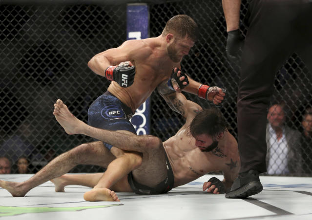 Calvin Kattar, top, throws a fight-ending flurry at Shane Burgos during a mixed martial arts bout at UFC 220, Saturday, Jan. 20, 2018, in Boston. Kattar won the bout. (AP Photo/Gregory Payan)