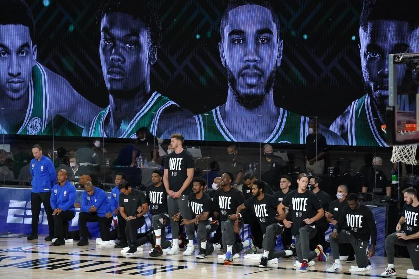 """Members of the Miami Heat wear shirts that read """"Vote,"""" during the national anthem before Game 1 of the NBA basketball Eastern Conference final against the Boston Celtics on Tuesday, Sept. 15, 2020, in Lake Buena Vista, Fla. (AP Photo/Mark J. Terrill)"""