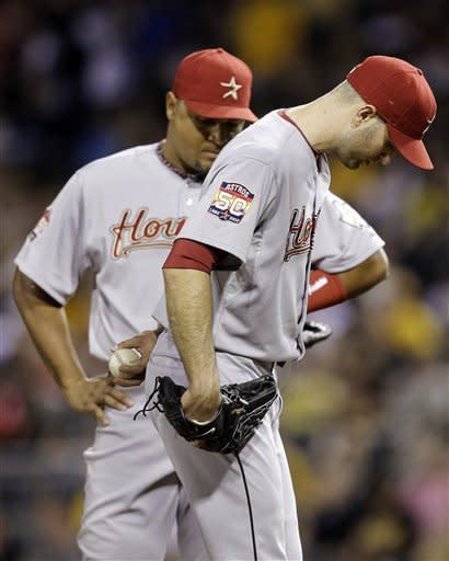 Houston Astros pitcher J.A. Happ, right, waits with Carlos Lee for manager Brad Mills to pull him during the sixth inning of a baseball game against the Pittsburgh Pirates in Pittsburgh, Saturday, May 12, 2012. The Pirates won 5-2. (AP Photo/Gene J. Puskar)