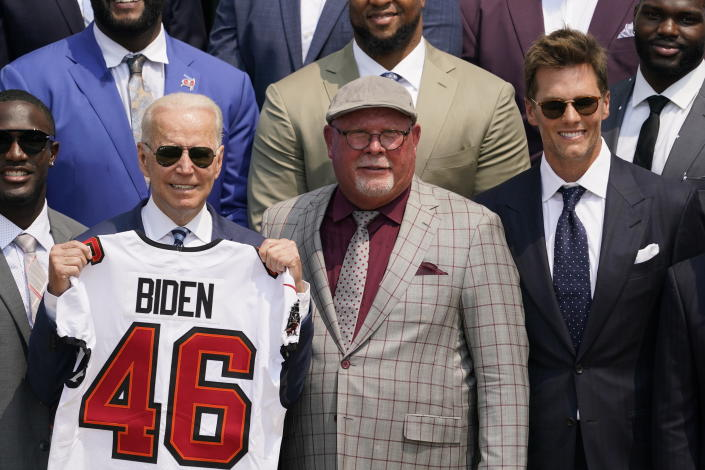 President Joe Biden, surrounded by members of the Tampa Bay Buccaneers, poses for a photo holding a jersey during a ceremony on the South Lawn of the White House, in Washington, Tuesday, July 20, 2021, where Biden honored the Super Bowl Champion Tampa Bay Buccaneers for their Super Bowl LV victory. Tampa Bay Buccaneers quarterback Tom Brady, right, and Tampa Bay Buccaneers head coach Bruce Arians look on. (AP Photo/Andrew Harnik)