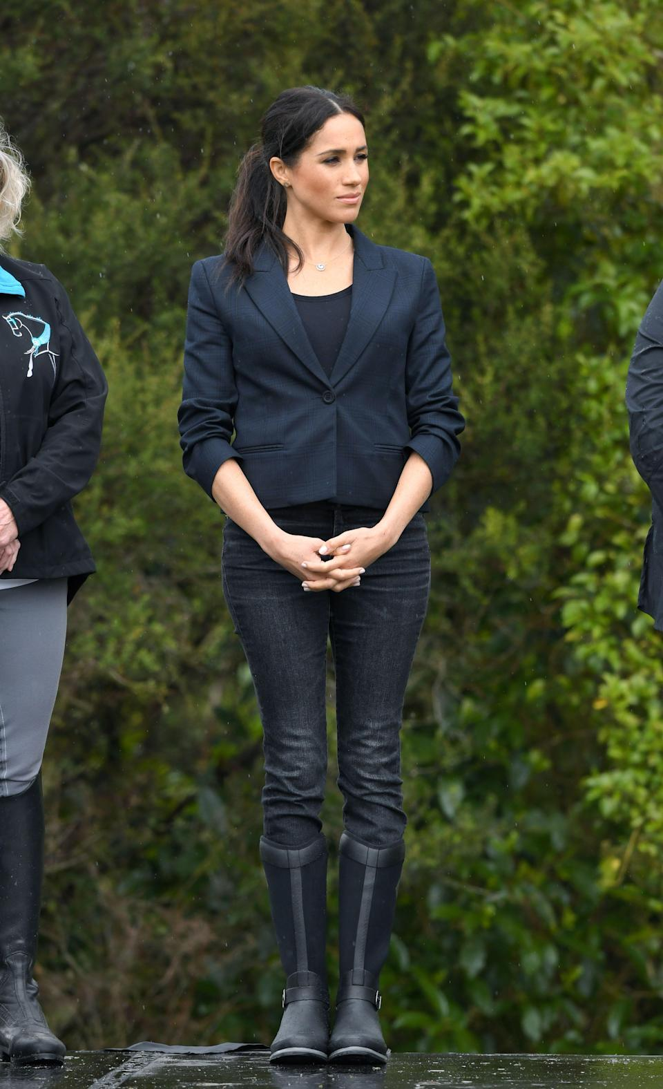 """<p>For the overcast days outdoors, Markle wore <a href=""""https://www.muckbootcompany.co.uk/womens-reign-tall-equestrian-boot.html"""" rel=""""nofollow noopener"""" target=""""_blank"""" data-ylk=""""slk:The Original Muck Boot Company's Reign tall boots"""" class=""""link rapid-noclick-resp"""">The Original Muck Boot Company's Reign tall boots</a>, with <a href=""""https://www.net-a-porter.com/gb/en/Shop/Designers/JCrew?cm_mmc=GoogleUK--c-_-NAP_EN_UK_London-_-NAP+-+INTL+-+London+-+Designer_J.Crew+-+BT--J.Crew+-+Alone+-+Phrase-_-j+crew_p_kwd-71021491_INTL&gclid=EAIaIQobChMIsOHJ-oOu3gIVCOd3Ch3fpwFZEAAYAiAAEgJ9sPD_BwE&gclsrc=aw.ds&pn=1&npp=60&image_view=product&dScroll=0"""" rel=""""nofollow noopener"""" target=""""_blank"""" data-ylk=""""slk:J.Crew"""" class=""""link rapid-noclick-resp"""">J.Crew</a> <a href=""""https://www.jcrew.com/uk/p/womens_category/denim_jeans/highrise/9-high-rise-toothpick-jean-in-charcoal-wash/H2651?color_name=charcoal-wash"""" rel=""""nofollow noopener"""" target=""""_blank"""" data-ylk=""""slk:jeans"""" class=""""link rapid-noclick-resp"""">jeans</a>, a <a href=""""https://www.lavenderhillclothing.com/collections/scoop-neck/products/essentialshortsleevetshirt"""" rel=""""nofollow noopener"""" target=""""_blank"""" data-ylk=""""slk:Lavender Hill t-shirt"""" class=""""link rapid-noclick-resp"""">Lavender Hill t-shirt</a> and a <a href=""""https://www.karenwalker.com/product/fathom-jacket?i=60027-01&u=6400000548795"""" rel=""""nofollow noopener"""" target=""""_blank"""" data-ylk=""""slk:Karen Walker blazer"""" class=""""link rapid-noclick-resp"""">Karen Walker blazer</a>.</p>"""