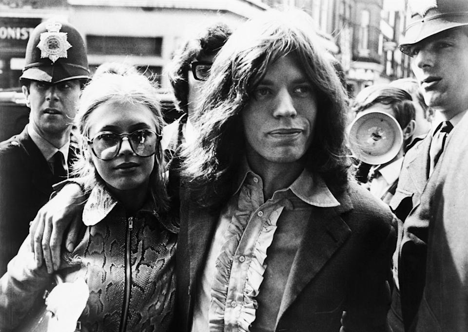 Mick Jagger of the Rolling Stones and girlfriend, singer Marianne Fiathfull, arrive at Magistrate's Court early May 29 to face charges of possessing marijuana. The couple, arrested during a police raid on Jagger's apartment May 28, was released an $120 bond.