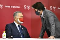 In this file photo taken on December 4, 2020, Yoshiro Mori (L) chats with Olympic Minister Seiko Hashimoto (R)