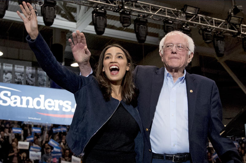In this Feb. 10, 2020 file photo, Democratic presidential candidate Sen. Bernie Sanders, I-Vt., right, and Rep. Alexandria Ocasio-Cortez, D-N.Y. wave to supporters at campaign stop at Whittemore Center Arena at the University of New Hampshire in Durham, N.H. On Tuesday, May 5, federal Judge Analisa Torres ruled that the New York Democratic presidential primary must take place June 23 because canceling it would be unconstitutional. (AP Photo/File, Andrew Harnik)