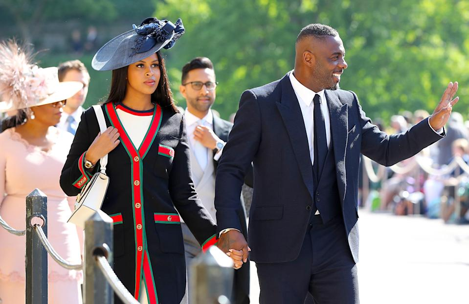 <p>The 'Luther' and 'The Wire' star is dapper in a black suit while his fiancee has opted for a statement hat. <em>[Photo: PA]</em> </p>