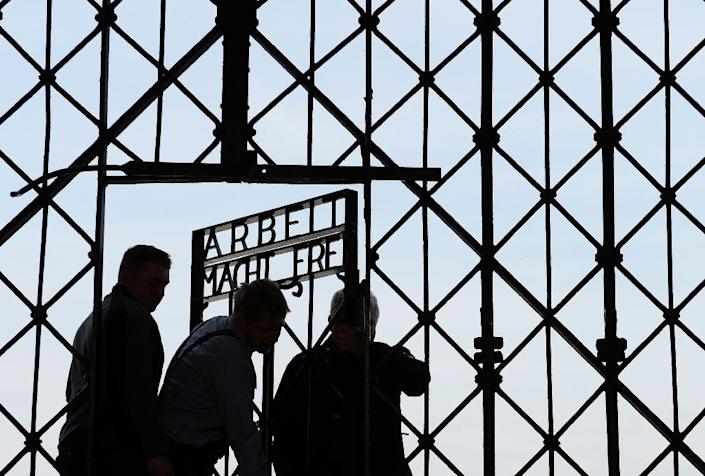 Workers fix the new entrance gate with the inscription 'Work sets you free' (Arbeit macht frei) in the former concentration camp in Dachau, southern Germany, on April 29, 2015 (AFP Photo/Christof Stache)