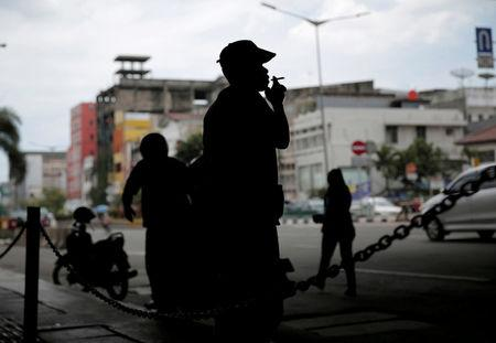 FILE PHOTO: A man smokes a cigarette on a street in Jakarta, Indonesia, March 15, 2017. REUTERS/Beawiharta/File Photo
