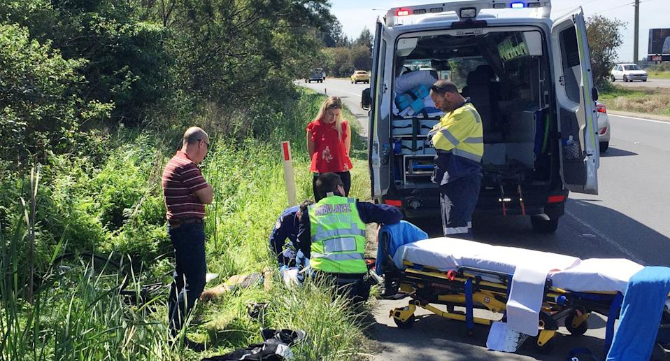 Cyclist Trevor Simmons unconscious on New England Highway at Tarro, NSW, after being hit by a car.