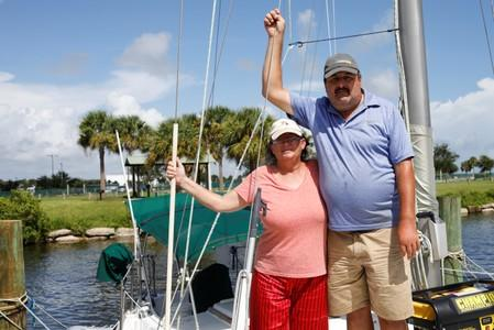 Lisa and Ned Keahey, who live in a sailboat and plan to stay aboard during Hurricane Dorian, pose for a photo at a marina in Titusville