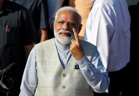 India's PM Modi shows his ink-marked finger after casting his vote outside a polling station during the third phase of general election in Ahmedabad