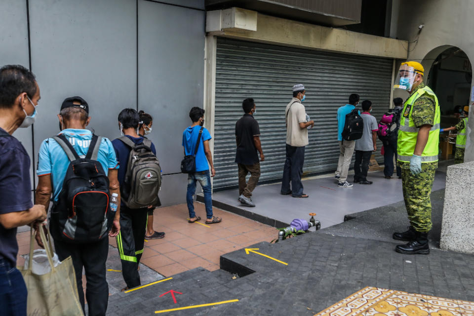 The homeless adhere to social distancing guidelines while queuing to collect food at the Pit Stop Community Cafe in Kuala Lumpur 30, 2020. — Picture by Firdaus Latif