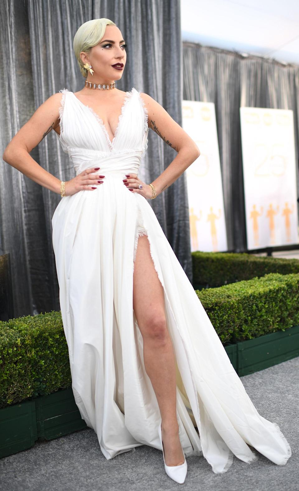 """<p>Wearing a white <a rel=""""nofollow noopener"""" href=""""https://www.popsugar.com/fashion/Lady-Gaga-Dior-Dress-SAG-Awards-2019-45717550"""" target=""""_blank"""" data-ylk=""""slk:Dior Haute Couture"""" class=""""link rapid-noclick-resp"""">Dior Haute Couture</a> with Jimmy Choo heels and Tiffany & Co. jewels.</p>"""