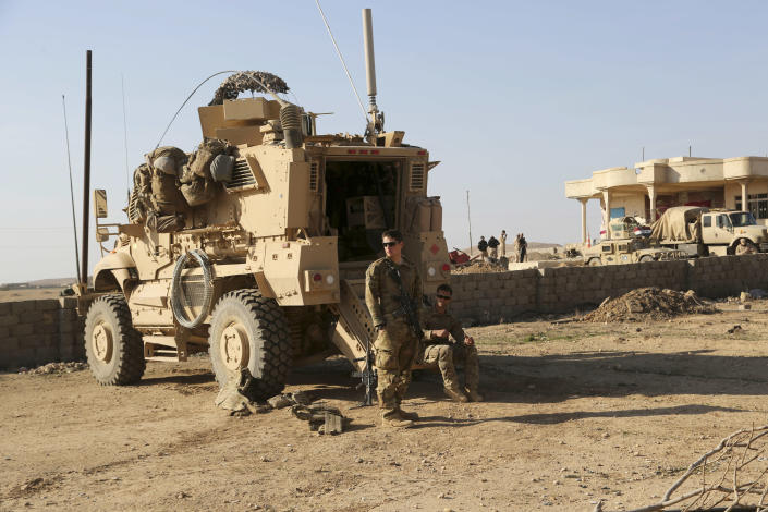 FILE - In this Feb. 23, 2017 file photo, U.S. Army soldiers stand outside their armored vehicle on a joint base with the Iraqi army, south of Mosul, Iraq. In a quest to root out Islamic State group hideouts over the summer, Iraqi forces on the ground cleared nearly 90 villages across a notoriously unruly northern province. But the much-touted operation still relied heavily on U.S. intelligence, coalition flights and planning assistance. (AP Photo/ Khalid Mohammed, File)