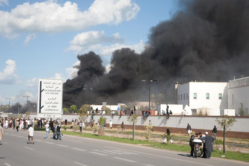 A pall of smoke rises above protesters after they set alight cars in the U.S. embassy parking lot in Tunis, Friday, Sept. 14, 2012.  some thousands of demonstrators massed outside the embassy and several were seen climbing the outer wall of the embassy grounds, an Associated Press reporter on the scene said. (AP Photo/Amine Landoulsi)