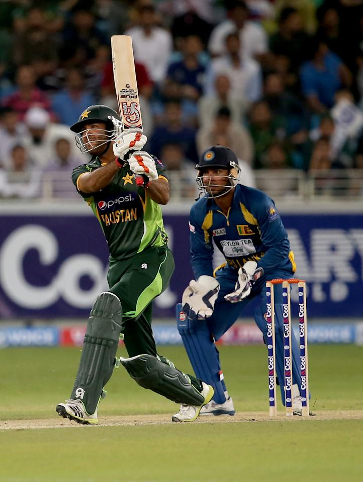DUBAI, UNITED ARAB EMIRATES - DECEMBER 13:  Sohaib Maqsood of Pakistan bats as Kumar Sangakkara looks on during the second Twenty20 International match between Pakistan and Sri Lanka at Dubai Sports City Cricket Stadium on December 13, 2013 in Dubai, United Arab Emirates.  (Photo by Francois Nel/Getty Images)
