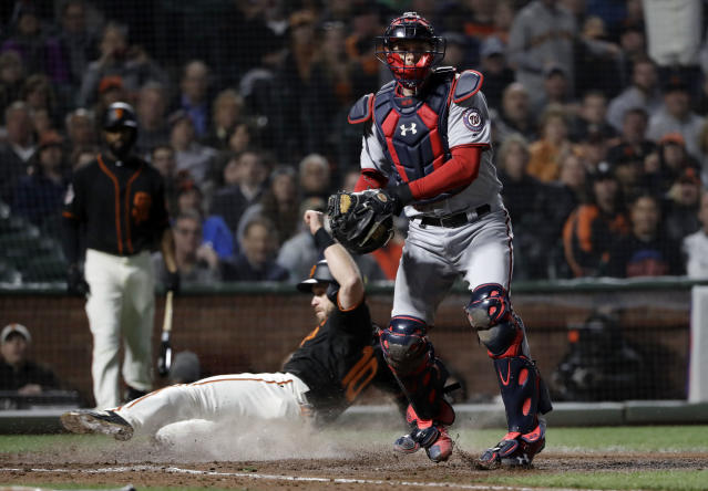 San Francisco Giants' Evan Longoria, left, scores past Washington Nationals catcher Matt Wieters on a fielder's choice after a ground ball by Mac Williamson during the fourth inning of a baseball game, Monday, April 23, 2018, in San Francisco. (AP Photo/Marcio Jose Sanchez)
