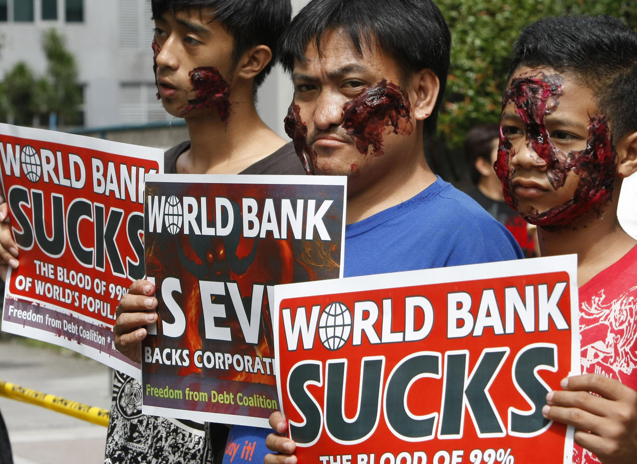 Protesters, sporting their Halloween costumes and make-up, display placards as they picket the World Bank office Thursday Oct.27, 2011 where visiting World Bank President Robert Zoellick is holding a news conference at suburban Mandaluyong, east of Manila, Philippines. Zoellick welcomed a deal clinched by European leaders to address their two-year debt crisis, saying it may have helped avert the spread of the financial turmoil to emerging markets that provide half of global economic growth. (AP Photo/Bullit Marquez)