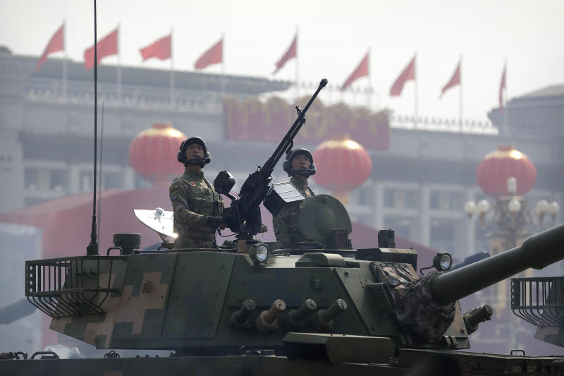 FILE - In this Oct. 1, 2019, file photo, Chinese tank crew members stand at attention during a parade to commemorate the 70th anniversary of the founding of Communist China in Beijing. China will boost defense spending by just 6.6% in 2020, the lowest rate in years as it battles an economic crisis brought on by the coronavirus outbreak, the government said Friday, May 22, 2020. (AP Photo/Mark Schiefelbein, File)