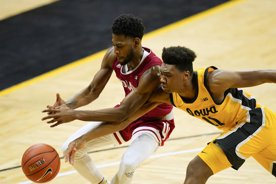 Iowa guard Tony Perkins tries to steal the ball from Indiana guard Al Durham, left, during the second half of an NCAA college basketball game, Thursday, Jan. 21, 2021, in Iowa City, Iowa. Indiana won 81-69. (AP Photo/Charlie Neibergall)