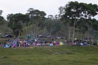 Migrants camp on a field in Acandi, Colombia, Tuesday, Sept. 14, 2021. The migrants, following a well-beaten, multi-nation journey towards the U.S., will continue their journey through the jungle known as the Darien Gap. (AP Photo/Fernando Vergara)
