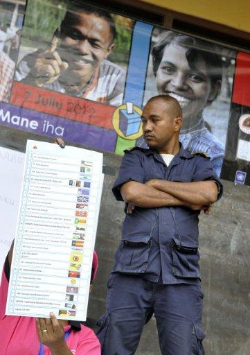 A local policeman guards the counting process for parliamentary elections by election officials (L) in Dili, on July 7. East Timor's voters went to the polls in parliamentary elections seen as a key test for the young and fragile democracy and likely to determine if UN peacekeepers can leave by the end of the year