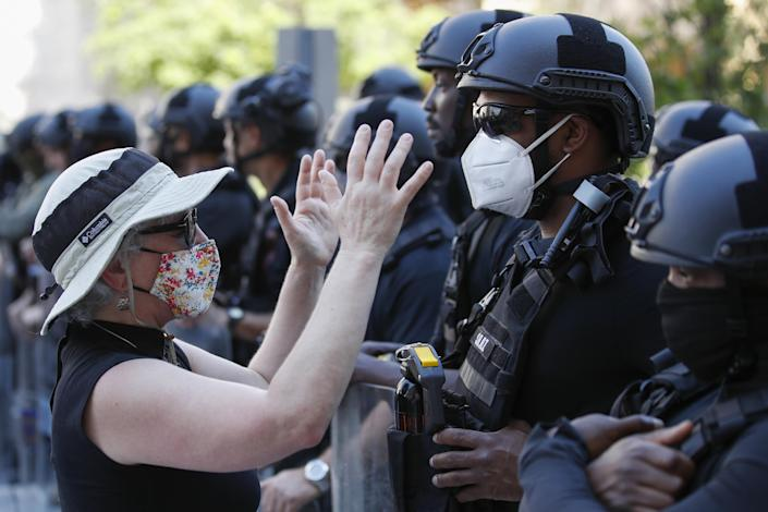 The Rev. Susan Wilder of Kirkwood Presbyterian Church in Springfield, Va., prays at the police line as demonstrators gather June 3 to protest the death of George Floyd near the White House in Washington.