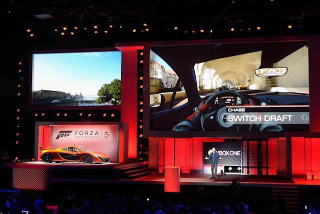 LOS ANGELES, CA - JUNE 10: Dan Greenawalt, developer of the video game Forza Motorsport, standing next to a McLaren sports car speak after unveiling Forza Motorsport 5 video game for Xbox during Microsoft Xbox news conference with a at the Electronic Entertainment Expo at the Galen Center on June 10, 2013 in Los Angeles, California. Thousands are expected to attend the annual three-day convention to see the latest games and announcements from the gaming industry. (Photo by Kevork Djansezian/Getty Images)