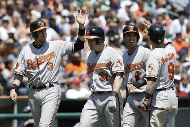 Baltimore Orioles catcher Taylor Teagarden (31) celebrates his three-run home run against the Detroit Tigers with Ryan Flaherty (3), J.J. Hardy (2) and Nate McLouth (9) in the fourth inning of a baseball game in Detroit, Wednesday, June 19, 2013. (AP Photo/Paul Sancya)