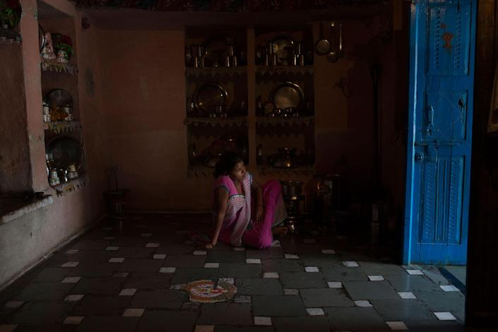 <p>Arti Khatik sits on the floor of her mother-in-law's house near Changedi, Udaipur, Rajasthan, India, where she has lived since she was 14 and moved in with her husband. July 2016. (Photo: Rafael Fabrés) </p>