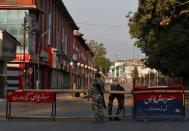 Indian Central Reserve Police Force officers put up a roadblock on an empty street during a lockdown on the first anniversary of the revocation of Kashmir's autonomy in Srinagar