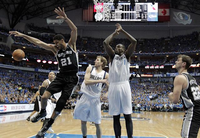 San Antonio Spurs' Tim Duncan (21) loses control of the ball after being fouled by Dallas Mavericks' Dirk Nowitzki (41) beneath the basket as Samuel Dalembert (1) and Tiago Splitter (22) watch in the first half of Game 4 of an NBA basketball first-round playoff series, Monday, April 28, 2014, in Dallas. (AP Photo/Tony Gutierrez)