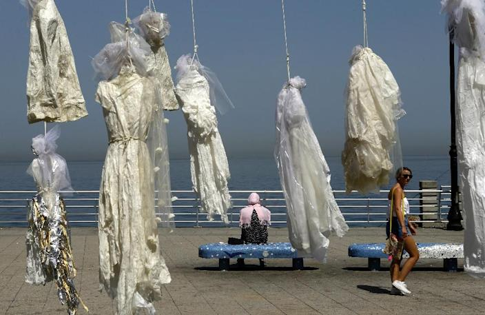 Lebanese activists use an installation of wedding dresses by Lebanese artist Mireille Honein at Beirut's Corniche to ramp up their campaign to press parliament to scrap Article 522 of Lebanon's penal code which allows rapists to escape punishement (AFP Photo/PATRICK BAZ)