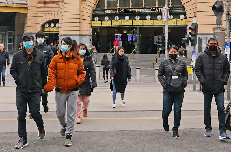 People leave Flinders Street Station wearing face masks on Sunday. Source: AAP