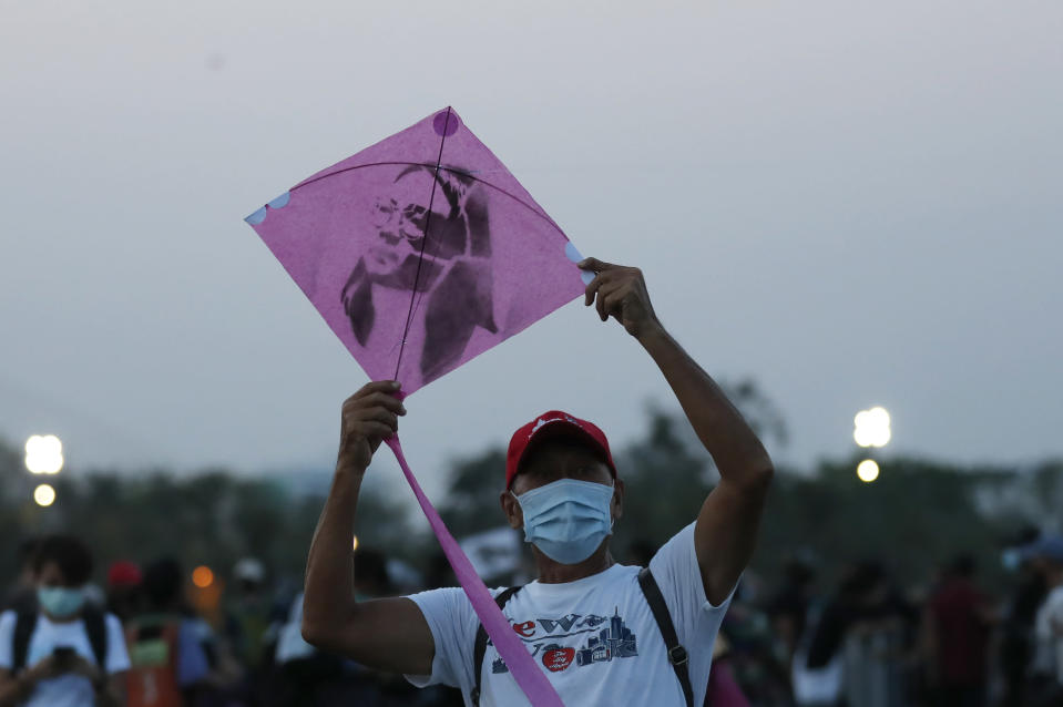 A man prepares to release a kite with an image of detained activist Panusaya Sithijirawattanakul which will be flown during a protest on the Sanam Luang grounds near the Grand Palace Saturday, March 20, 2021, in Bangkok, Thailand. Thailand's student-led pro-democracy movement is holding a rally in the Thai capital, seeking to press demands that include freedom for their leaders, who are being held without bail on charges of defaming the monarchy. (AP Photo/Sakchai Lalit)