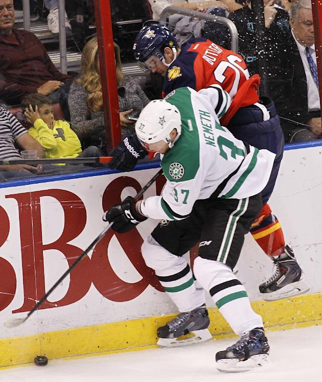 Dallas Stars defenseman Patrik Nemeth (37) and Florida Panthers right wing Bobby Butler (26) collide as they go for the puck during the first period of an NHL hockey game in Sunrise, Fla., Sunday, April 6, 2014. (AP Photo/Terry Renna)