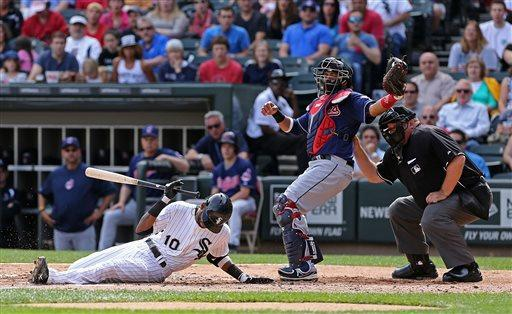Chicago White Sox' Alexei Ramirez hits the dirt from a high inside pitch by Cleveland Indians pitcher Ubaldo Jimenez while catcher Carlos Santana catches and umpire Wally Bell calls the play in the second inning of a baseball game in Chicago, Saturday, June 29, 2013. (AP Photo/Charles Cherney)