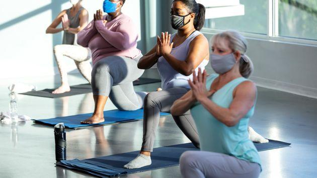 A multi-ethnic group of four women taking a yoga class, in a crescent lunge pose on knee with prayer hands. They are indoors, side by side, with the focus on the African-American woman second from right. She is in her 30s. They are wearing protective face masks, trying to prevent the spread of coronavirus during the COVID-19 pandemic. (Photo: kali9 via Getty Images)