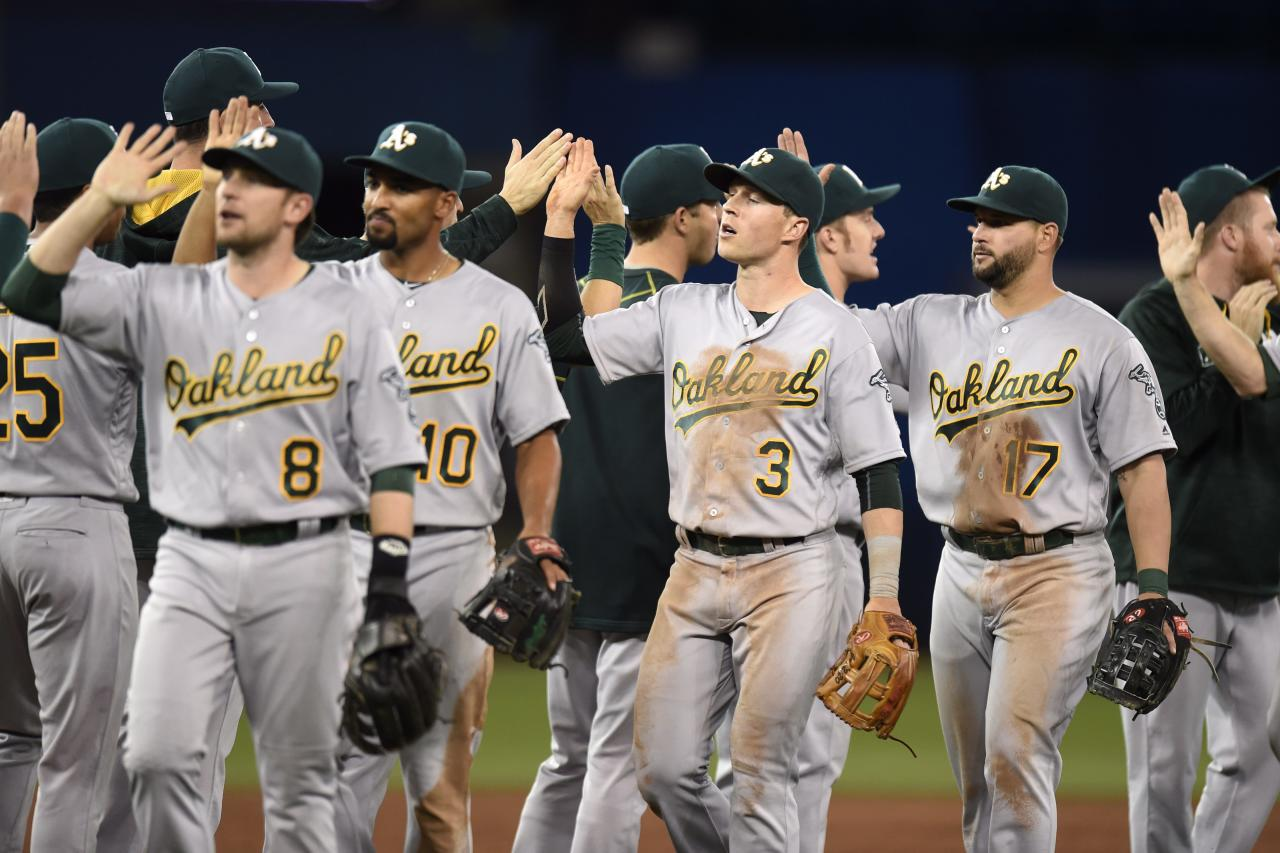 Oakland Athletics celebrate an 8-5 win over the Toronto Blue Jays in a baseball game Friday, April 22, 2016, in Toronto. (Frank Gunn/The Canadian Press via AP)