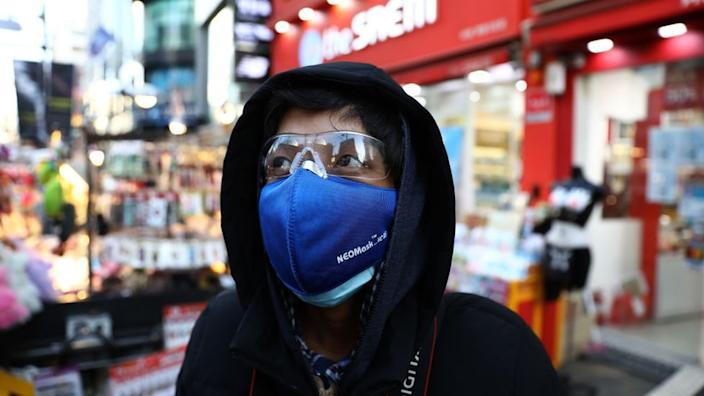 A man wear mask to prevent the coronavirus (COVID-19) walk along the Myungdong shopping district on February 23, 2020