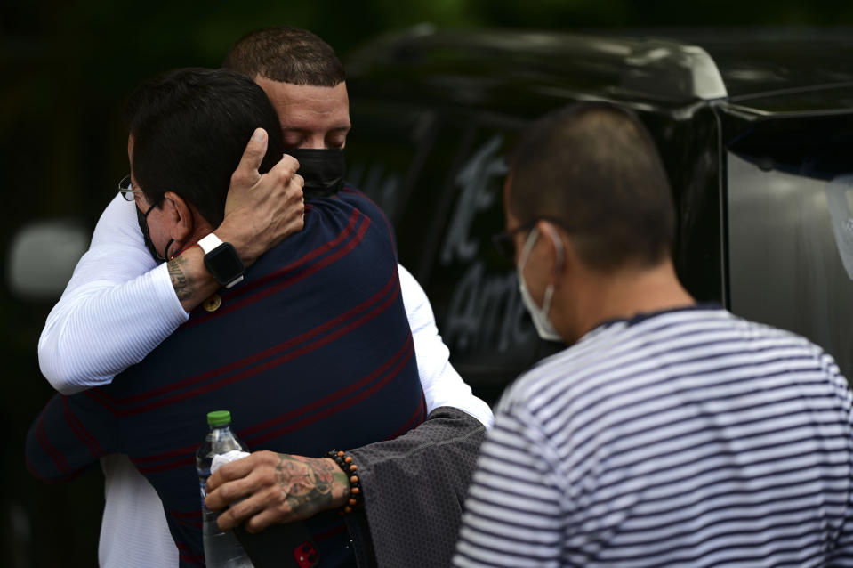 Jose Antonio Rodriguez, left, is embraced by a relative as he arrives at a wake for his 27-year-old-daughter Keishla Rodriguez, whose lifeless body was found in a lagoon Saturday, at a funeral home in San Juan, Puerto Rico, Thursday, May 6, 2021. A federal judge on Monday ordered Puerto Rican boxer Felix Verdejo held without bail after he was charged with the death of Keishla Rodriguez and with intentionally killing the unborn child she was carrying. (AP Photo/Carlos Giusti)