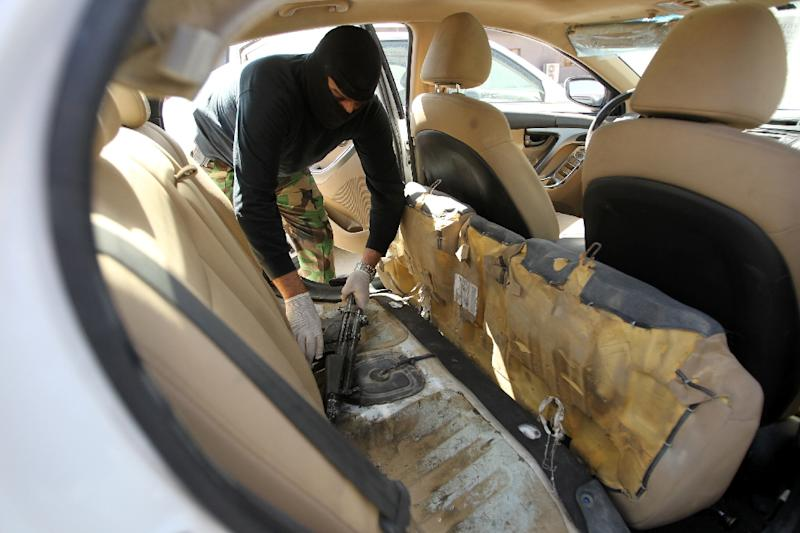 A member of the Iraqi security forces pulls out a machine-gun on March 16, 2015, hidden under the backseat inside a car seized in Baghdad (AFP Photo/Ali Al-Saadi)