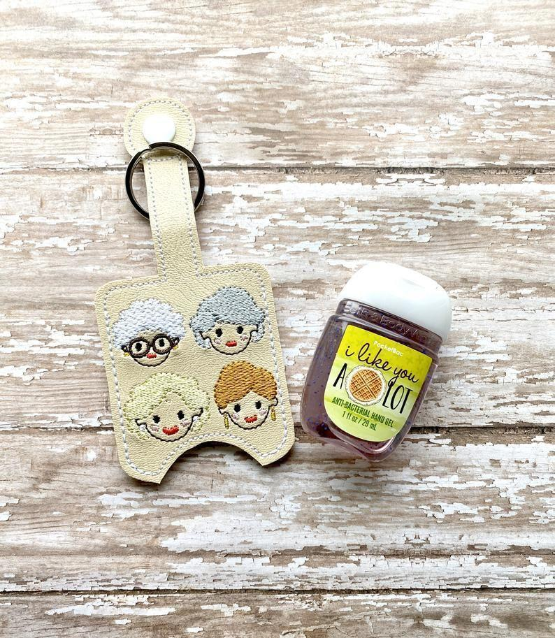 """<p><strong>WhileEllieDreams</strong></p><p>etsy.com</p><p><strong>$9.50</strong></p><p><a href=""""https://go.redirectingat.com?id=74968X1596630&url=https%3A%2F%2Fwww.etsy.com%2Flisting%2F789146259%2Fgolden-girls-sanitizer-holder-golden&sref=https%3A%2F%2Fwww.housebeautiful.com%2Fshopping%2Fg29038509%2Fgolden-girls-gift-ideas%2F"""" rel=""""nofollow noopener"""" target=""""_blank"""" data-ylk=""""slk:Shop Now"""" class=""""link rapid-noclick-resp"""">Shop Now</a></p>"""