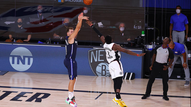Luka Doncic is pictured shooting over LA Clippers opponent Reggie Jackson to win the game.
