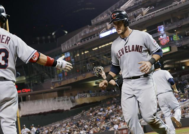 Cleveland Indians' Yan Gomes, right, is greeted by Nick Swisher as he scores on a single by Michael Brantley off Minnesota Twins pitcher Josh Roenicke in the eighth inning of a baseball game, Thursday, Sept. 26, 2013, in Minneapolis. The Indians won 6-5. Gomes hit a two-run home run in the fourth. (AP Photo/Jim Mone)
