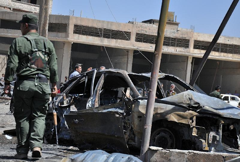 A member of the Kurdish security forces walks at the site of a suicide bomb attack in the industrial district of Qamishli, in northeastern Syria, in August 2015 (AFP Photo/Delil Souleiman)