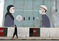 A man wearing a protective face mask to help curb the spread of the coronavirus, walks past a painted wall of Ministry of Public Health, which guides social distancing in Kabul, Afghanistan, Saturday, May 29, 2021. (AP Photo/Rahmat Gul)
