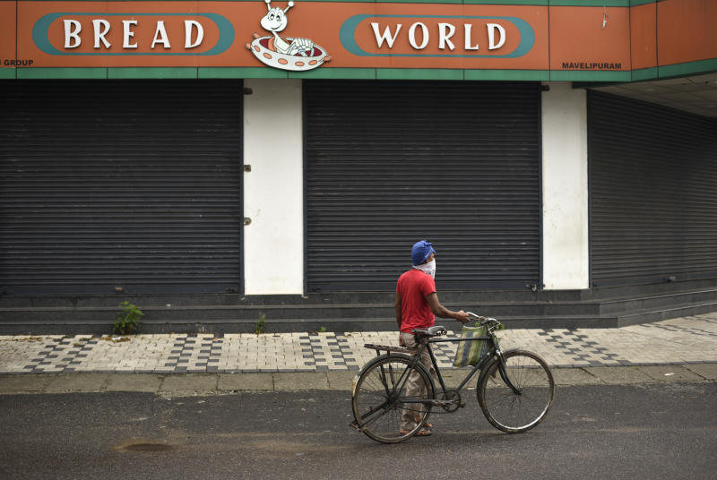 An Indian laborer walks with his bicycle past a bread shop before it opens in the morning in Kochi, Kerala state, India, Friday, May 22, 2020. India's central bank on Friday cut its key interest rate to 4% to revive the economy severely hit the coronavirus outbreak and a two-month lockdown. (AP Photo/R S Iyer)