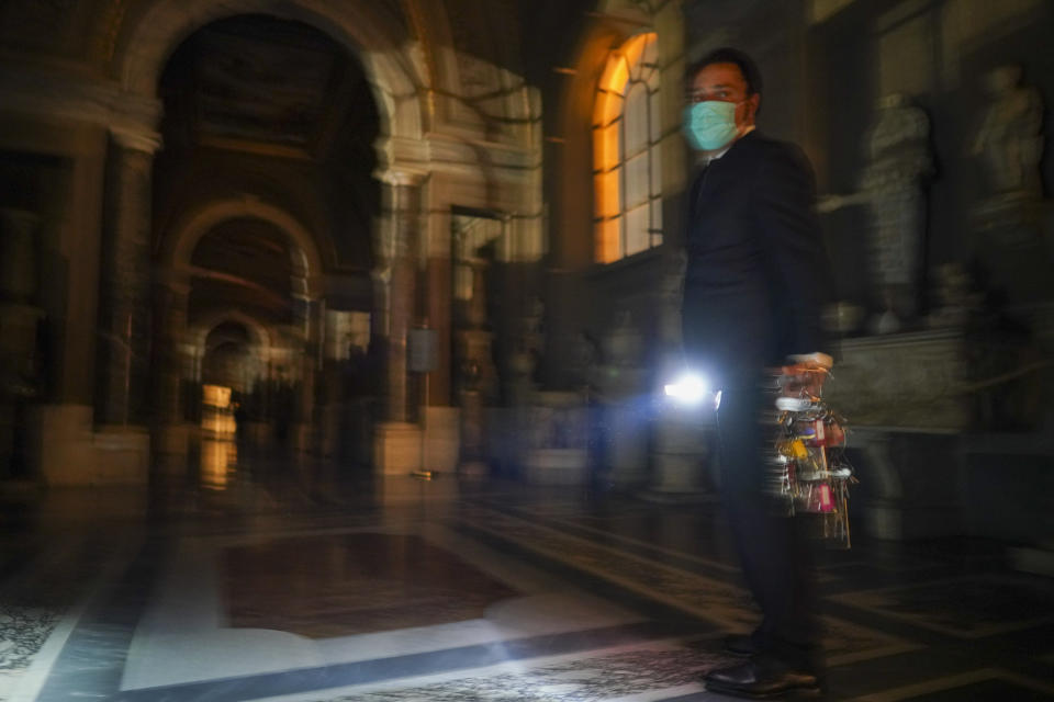 "Gianni Crea, the Vatican Museums chief ""Clavigero"" key-keeper, holds a torch and a bunch of keys as he walks to open the museum's rooms and sections, at the Vatican, Monday, Feb. 1, 2021. Crea is the ""clavigero"" of the Vatican Museums, the chief key-keeper whose job begins each morning at 5 a.m., opening the doors and turning on the lights through 7 kilometers of one of the world's greatest collections of art and antiquities. The Associated Press followed Crea on his rounds the first day the museum reopened to the public, joining him in the underground ""bunker"" where the 2,797 keys to the Vatican treasures are kept in wall safes overnight. (AP Photo/Andrew Medichini)"